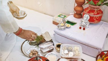 The indian prayer prepraing the worship items for thread ceremony (puja, pooja) of indian wedding event with Ganesha statue (Hindu god of wisdom)